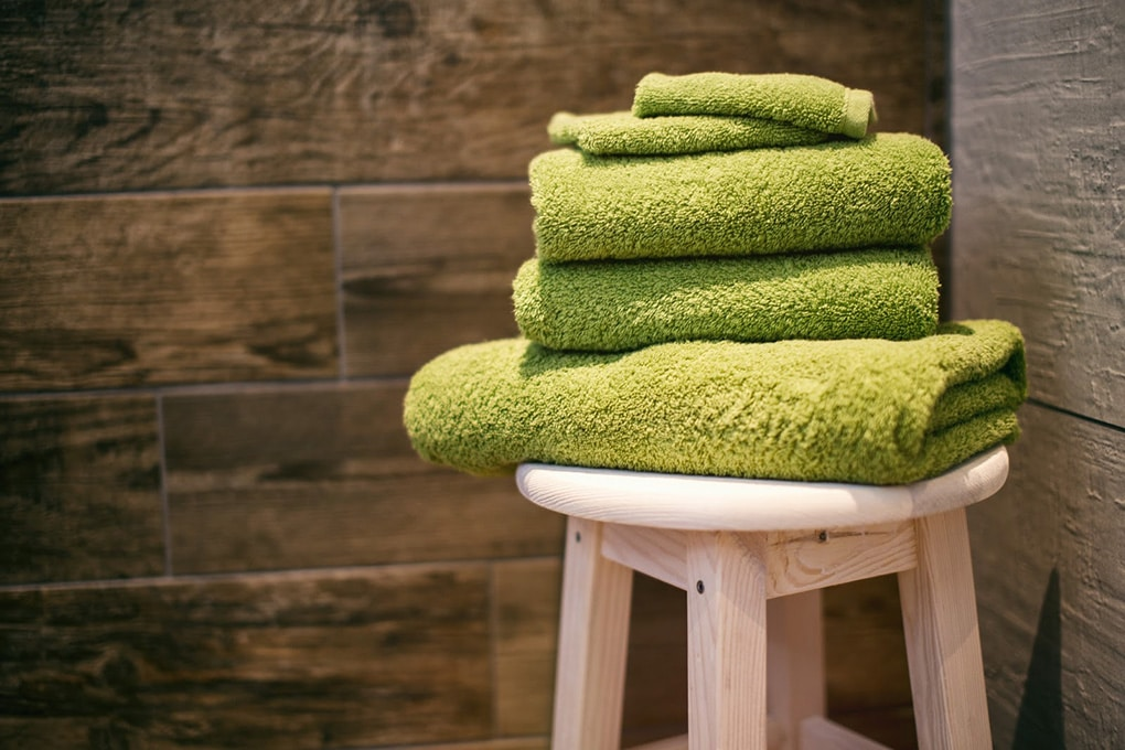 5 green towels on top of a stool