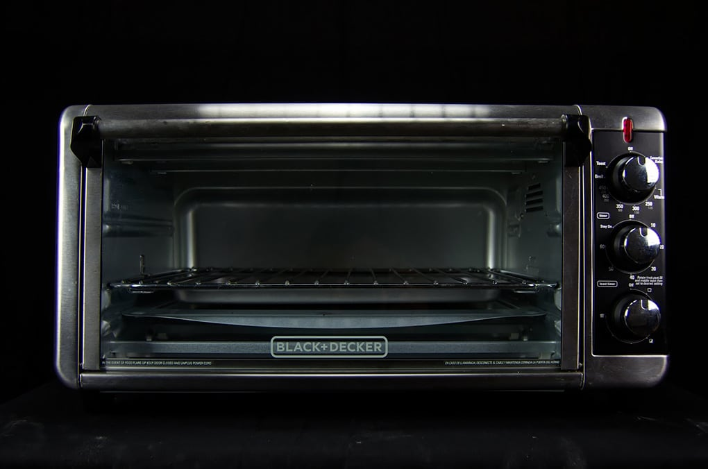 Microwaves sitting against a black background